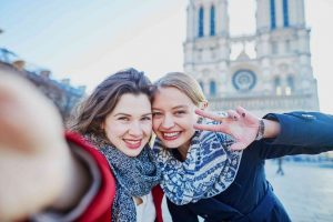 girls taking selfie in Paris at the Notre Dame